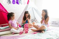 Friends Looking At Tower Of Wooden Blocks During Slumber Party. Surprised little best friends looking at tower of wooden blocks during slumber party at home royalty free stock photos