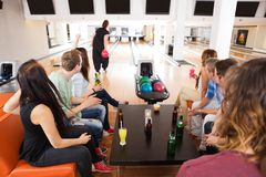 Friends Looking At Woman Bowling in Club. Group of young friends looking at women bowling in club royalty free stock photo
