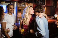 Friends looking at woman embracing man in club. Friends looking at woman embracing man while standing in club stock image