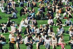 Friends Lunch Break. Family, friends, colleagues and workmates relaxing in the sunshine on a grassy bank in Kings Cross, London during a long lunch break Royalty Free Stock Photo