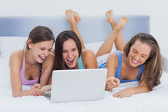 Friends lying on bed with laptop Stock Photo