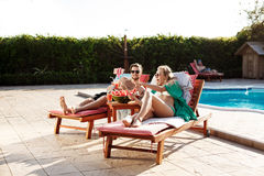 Friends lying on chaises near swimming pool, making selfie, smiling. Royalty Free Stock Image