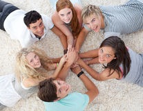 Friends lying on the floor with hands together Royalty Free Stock Photography