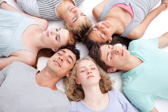 Friends lying on floor with heads together Stock Image