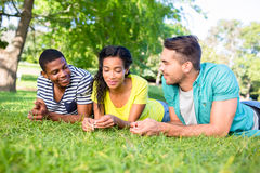 Friends lying on grass at campus. Friends talking while lying on grass at college campus Stock Photos