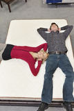 Friends lying on mattress with hands behind head in furniture store Royalty Free Stock Photo