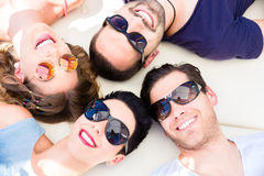 Friends lying in sand on beach Royalty Free Stock Image