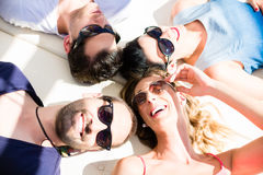 Friends lying in sand on beach Royalty Free Stock Photos