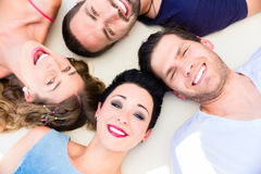 Friends lying in sand on beach Royalty Free Stock Images