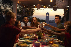 Friends make a toast at a dinner party on a patio, close up Stock Image