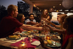 Friends make a toast at a dinner party on a patio, close up stock photos