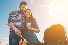 Friends making barbecue and having lunch in the nature. Couple having fun while eating and drinking at a pic-nic - Happy Royalty Free Stock Photography
