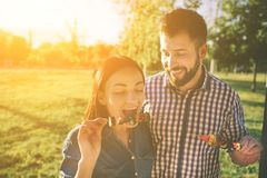 Friends making barbecue and having lunch in the nature. Couple having fun while eating and drinking at a pic-nic - Happy Stock Photo