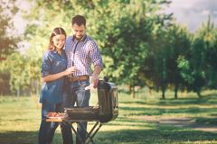 Friends making barbecue and having lunch in the nature. Couple having fun while eating and drinking at a pic-nic - Happy. People at bbq party royalty free stock photo