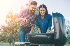 Friends making barbecue and having lunch in the nature. Couple having fun while eating and drinking at a pic-nic - Happy. People at bbq party stock images