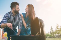 Friends making barbecue and having lunch in the nature. Couple having fun while eating and drinking at a pic-nic - Happy Royalty Free Stock Images