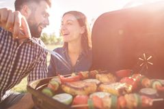 Friends making barbecue and having lunch in the nature. Couple having fun while eating and drinking at a pic-nic - Happy Stock Image