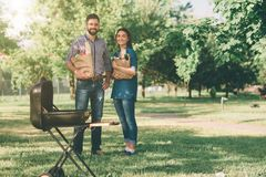 Friends making barbecue and having lunch in the nature. Couple having fun while eating and drinking at a pic-nic - Happy. People at bbq party stock photography