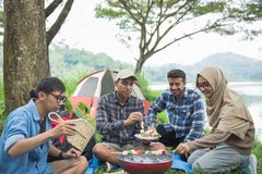 Friends making a barbecue together outdoors. In the nature Stock Image