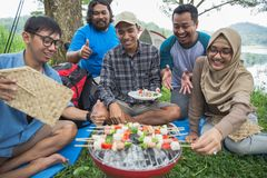 Friends making a barbecue together outdoors. In the nature Royalty Free Stock Images