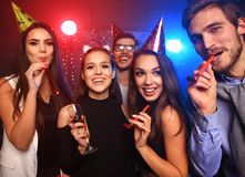 Friends making big party in the night. Five people throwing confetti and drinking champagne. Stock Photo