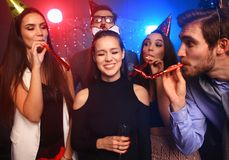 Friends making big party in the night. Five people throwing confetti and drinking champagne. Royalty Free Stock Photos