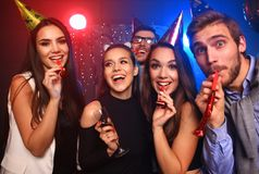 Friends making big party in the night. Five people throwing confetti and drinking champagne. Stock Photos