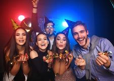Cheerful young people showered with confetti on a club party. Friends making big party in the night. Four people throwing confetti and drinking champagne royalty free stock photography