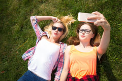 Friends making selfie and having fun in park. Happy teenage girls spend time together in the city. Friends making selfie and having fun in park. Happy teenage Royalty Free Stock Photos