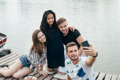 Friends making selfie sitting on pier with lake background while royalty free stock photos