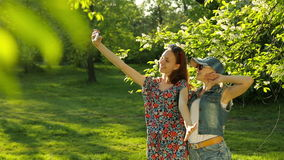 Friends making selfie. Two beautiful young women making selfie. On the park stock video footage