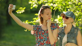 Friends making selfie. Two beautiful young women making selfie. On the park stock footage