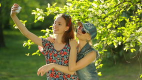 Friends making selfie. Two beautiful young women making selfie. Friends making selfie. Two beautiful young women making selfie on the park stock video footage