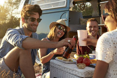Friends making a toast at a picnic beside their camper van Royalty Free Stock Photo