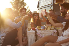Friends making a toast at a picnic beside their camper van Stock Images