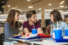 Friends At The Mall. Friends Eating Fast Food And Talking At The Mall Royalty Free Stock Image