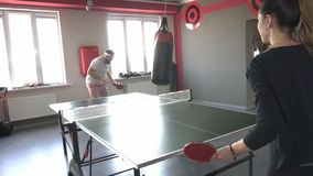 Friends a man with a beard and a beautiful pretty girl playing table tennis in the new gym, sports and health, slow stock video footage