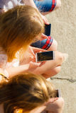 Friends man and women using mobile phones. Friends texting using mobile phones outdoor. Women and men browsing internet on smartphone. Summer relax Stock Photos