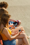Friends man and women using mobile phones. Friends texting using mobile phones outdoor. Young women and men browsing internet on smartphone. Summer relax Royalty Free Stock Image