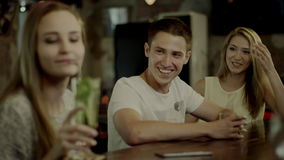 Friends meeting in a bar. Two girls talking at a bar counter when young smiling man joins them in a bar everybody happy stock video