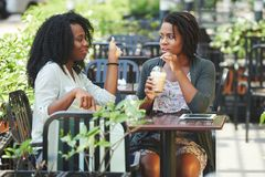 Friends meeting in cafe. Two pretty Africa-American women drinking cocktails and chatting in cafe Stock Photo