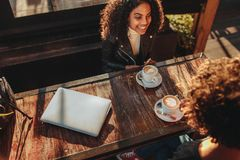 Two women talking over coffee at a coffee shop. Friends meeting at a coffee shop. Two women sitting across a table with coffee cups and a laptop royalty free stock images
