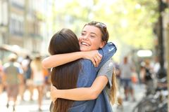 Friends meeting and cuddling in the street. Two happy friends meeting and cuddling in the street stock photos