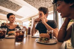 Friends meeting at a fast food restaurant. Group of friends meeting at a fast food restaurant. Man and women talking and having stack burger at a restaurant royalty free stock photography