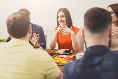 Pretty happy girl with friends at festive table dinner party. Friends meeting. Group of happy people talking and drinking wine at party dinner table in cafe Royalty Free Stock Images