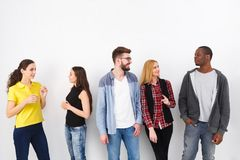 Friends meeting on white background. Multiethnic young people having conversation. Teamwork, brainstorming, fun concept stock photography