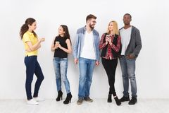 Friends meeting on white background. Multiethnic young people having conversation. Teamwork, brainstorming, fun concept stock photos