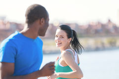 Friends meeting. Young couple smiling to each other while joggin Royalty Free Stock Image