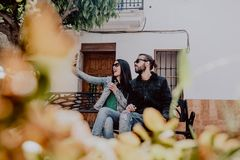 Friends, man and woman sitting on a bench in the square, happy to take selfies royalty free stock images