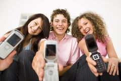 Friends with mobile phones. Three happy friends sitting and showing mobile phone to the camera. Looking at camera. Low angle view Stock Images